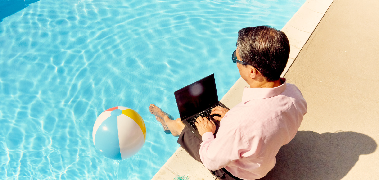 Man working on his laptop relaxing by the pool.