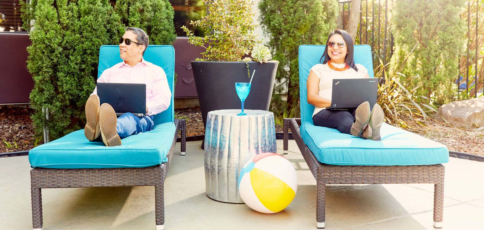 Couple Working on Laptops Pool Side