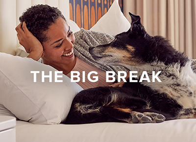 Joie de Vivre Hotels Summer Campaign woman laying in bed with dog
