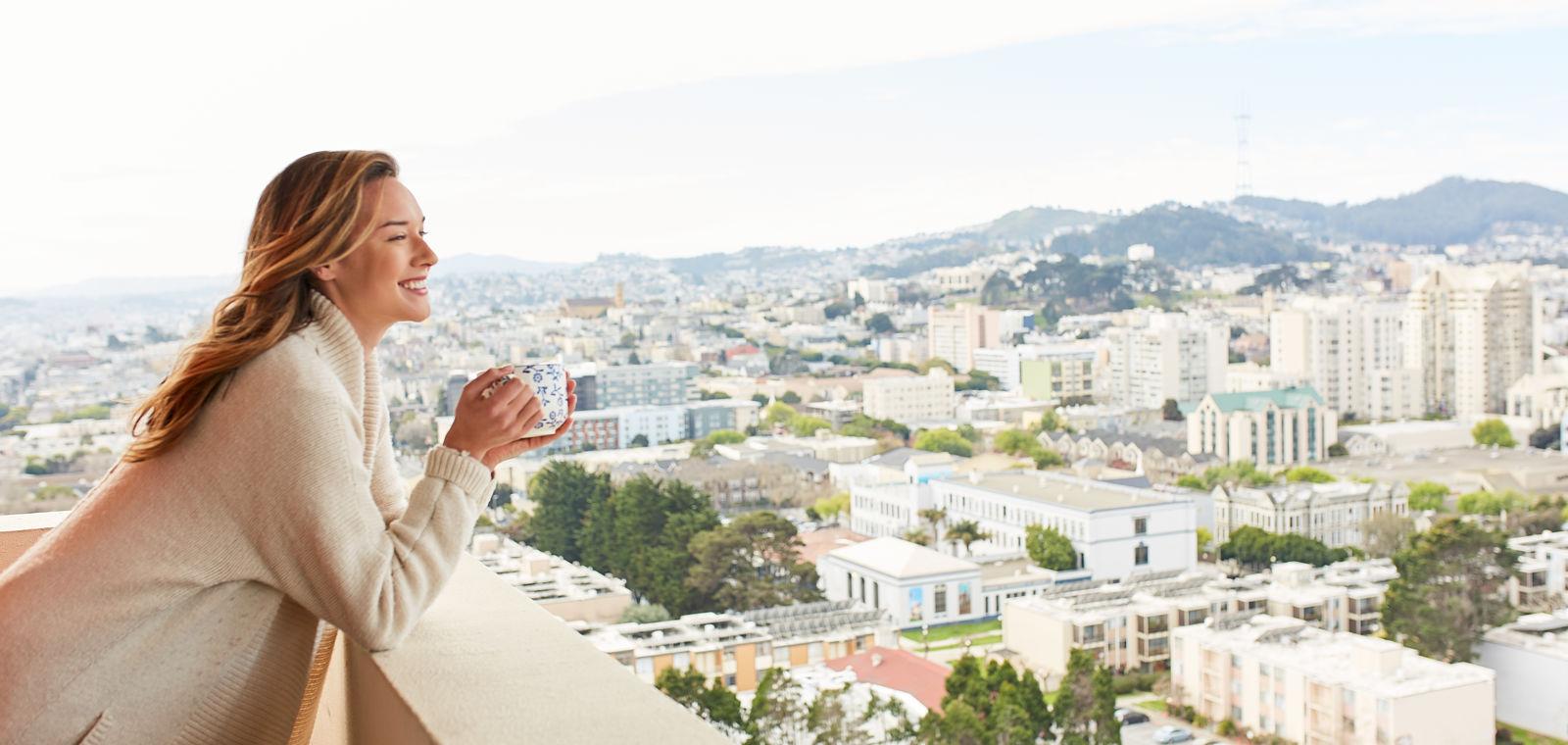 Woman Drinking Coffee on Balcony