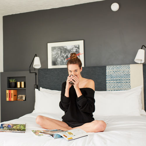 Woman Sitting on Bed with Coffee and Magazines
