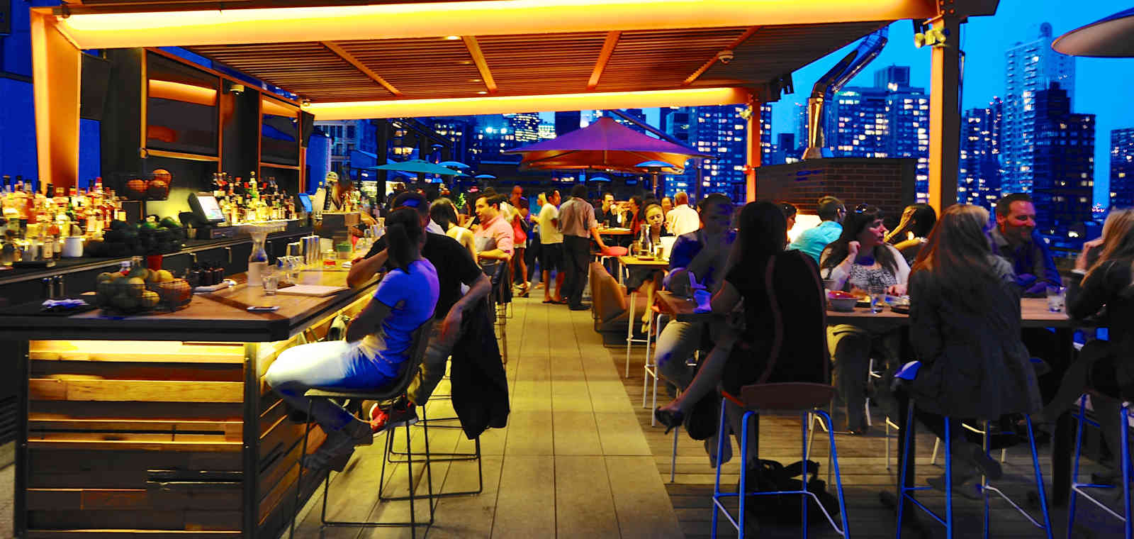 Guests Sitting At Rooftop Bar In The Evening