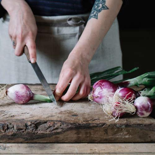 Chef chopping fresh radishes.